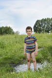 Dirty rural boy stands barefoot in a puddle. Stock Photography
