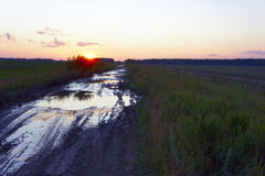 Dirty rural road among fields at sunset. The Dirty rural road among fields at sunset stock photography