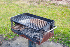 Dirty rusted barbecue grill near grass. Royalty Free Stock Photography