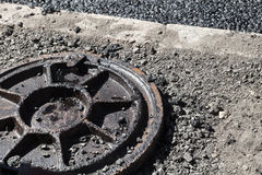 Dirty rusted sewer manhole cover on a roadside. Urban road under construction, asphalting in progress. Dirty rusted sewer manhole cover lays on a roadside stock photos