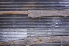 Dirty rusty black gray metal fence with wooden planks. horizontal lines. rough texture texture. A dirty rusty black gray metal fence with wooden planks royalty free stock images
