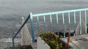 Dirty and rusty blue metal railing by the sea
