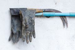 Dirty rusty sickle and dirty rubber gloves hanging on wall Royalty Free Stock Image