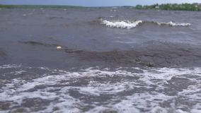 Dirty sea after a storm. Dirty waves with white foam carry garbage to the shore after the storm, slowed down traffic, slow-motion stock footage