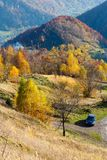 Dirty secondary road in autumn Carpathian mountain, Ukraine. Unrecognizable car on dirty secondary road to mountain pass in autumn Carpathian mountains and Stock Images