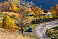 Dirty secondary road in autumn Carpathian mountain, Ukraine. Unrecognizable car on dirty secondary road to mountain pass in autumn Carpathian mountains and Stock Photos