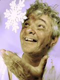 Dirty Senior Man with Snowflake in Winter. Happy, messy, baby-boomer man in winter catching a snowflake Stock Photography