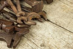Dirty set of hand tools on a wooden background. Old rusty tools. Equipment for locksmith and metalworking shop. Royalty Free Stock Photo
