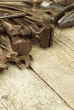 Dirty set of hand tools on a wooden background. Old rusty tools. Equipment for locksmith and metalworking shop. Royalty Free Stock Images