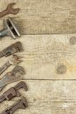 Dirty set of hand tools on a wooden background. Old rusty tools. Equipment for locksmith and metalworking shop. Stock Photo