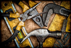 Dirty set of hand tools on a wooden panel Royalty Free Stock Images