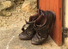 Dirty shoes outside door. A pair of old dirty men's shoes left perched outsidethe house leaning against the door in a small village in france. Focus on front royalty free stock images