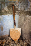 Dirty shovel in the corner of an old wall Royalty Free Stock Photography
