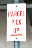 Dirty Sign Stating PARCEL PICK UP with Right Arrow. Dirty red and white sign on post stating PARCEL PICK UP with arrow pointing right royalty free stock images