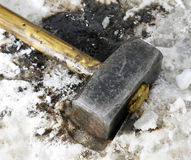 Dirty sledgehammer lies in the snow Stock Photography