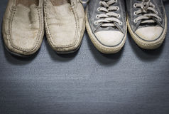 Dirty sneakers and white leather shoes on plywood gray floor. For copy space Stock Photography
