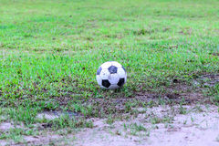 Dirty soccer ball in wet field