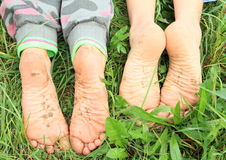Dirty soles of bare feet. Four dirty soles of bare feet of two little girls - kids lying on green grass Royalty Free Stock Photography