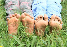 Dirty soles of bare feet. Of two little girls - kids sitting on green grass stock photography