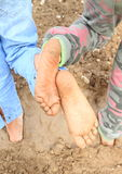 Dirty soles of bare feet. Of two little girls - kids standing on muddy ground Royalty Free Stock Photography