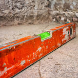 Dirty spirit level on a concrete surface. Used and dirty spirit level above a rough unfinished concrete wall Stock Photo