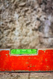 Dirty spirit level on a concrete surface. Used and dirty spirit level above a rough unfinished concrete wall Royalty Free Stock Images