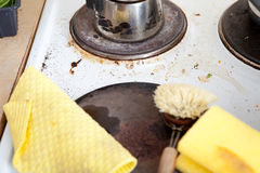 Dirty stove in domestic kitchen with used sponge, leftovers and pots Stock Photography