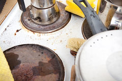 Dirty stove top in domestic kitchen. With leftovers, messy pots and espresso maker, yellow sponge and used scrubber royalty free stock photo