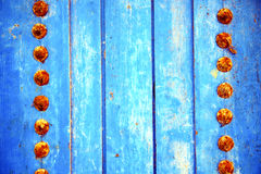Dirty stripped paint in the blue wood door and rusty Stock Images