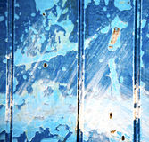 dirty stripped paint in the blue wood door and rusty nail Stock Photo