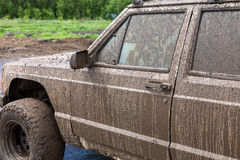 Dirty SUV after driving in the rain on extremely rural road. Dirty SUV after driving in the rain on extremely dirty rural road Royalty Free Stock Image