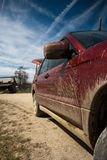 Dirty SUV on a mountain road. Image showing a dirty red SUV on a mountain road in Romania stock photo