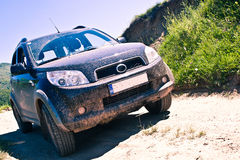 Dirty SUV on a mountain road. Image showing a dirty black SUV on a mountain road in Romania royalty free stock photo