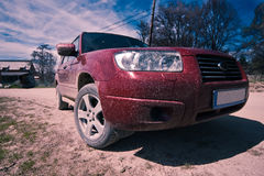 Dirty SUV on a mountain road. Image showing a dirty red SUV on a mountain road in Romania royalty free stock images