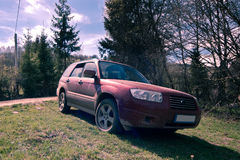 Dirty SUV on a mountain road. Image showing a dirty red SUV on a mountain road in Romania Royalty Free Stock Photos