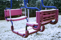 Dirty swing covered in snow Stock Images