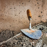 Dirty trowel above a concrete wall Stock Photos