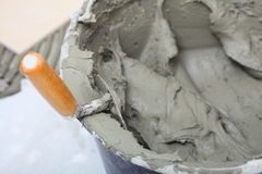 Dirty trowel and bucket on building site Royalty Free Stock Image