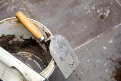 Dirty trowel and bucket on building site. Renovation at home Stock Images