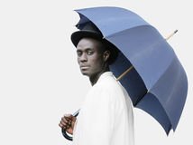 Dirty umbrella. Young black man with a blue umbrella wearing a bowler hat Stock Image