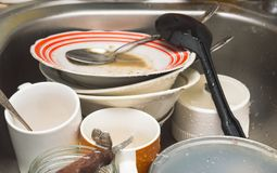 Unwashed kitchen utensils and dishes in the sink. Dirty unwashed kitchen utensils and dishes in the sink royalty free stock photo