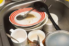Unwashed kitchen utensils and dishes in the sink. Dirty unwashed kitchen utensils and dishes in the sink stock photo