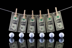 Dirty US dollar banknotes and golf balls Stock Images