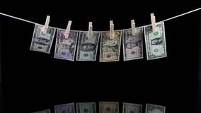 Dirty US dollar banknotes hanging from a clothesline. And reflecting in the glass stock video