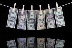 Dirty US dollar banknotes hanging from a clothesline Stock Photos