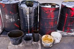 Dirty used colorful oil drums are modified to look like garbage cans in the engine room. Used engine oil in large barrels, buckets royalty free stock photography
