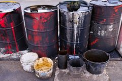 Dirty used colorful oil drums are modified to look like garbage cans in the engine room. Used engine oil in large barrels, buckets stock image