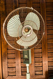 Dirty Vintage fan against wooden wall Stock Photography