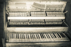 Dirty vintage upright piano in black and white. Old antique piano with dirty keys and an exposed inner workings in black and white Stock Photo