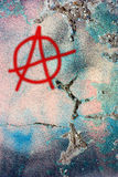 Dirty wall with anarchy symbol. Anarchy symbol on dirty painted wall. graffiti on grunge scratched cracked plaster Royalty Free Stock Image